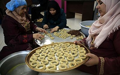 Palestinian women prepare traditional cookies ahead of the Eid al-Fitr festivities, celebrating the end of the holy Muslim fasting month of Ramadan, in Beit Lahia in the northern Gaza Strip on May 29, 2019. (MOHAMMED ABED / AFP)