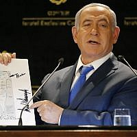 Prime Minister Benjamin Netanyahu displays a map of Israel indicating the Golan Heights are inside the state's borders, signed by US president Donald Trump on May 30, 2019. (Thomas COEX / AFP)