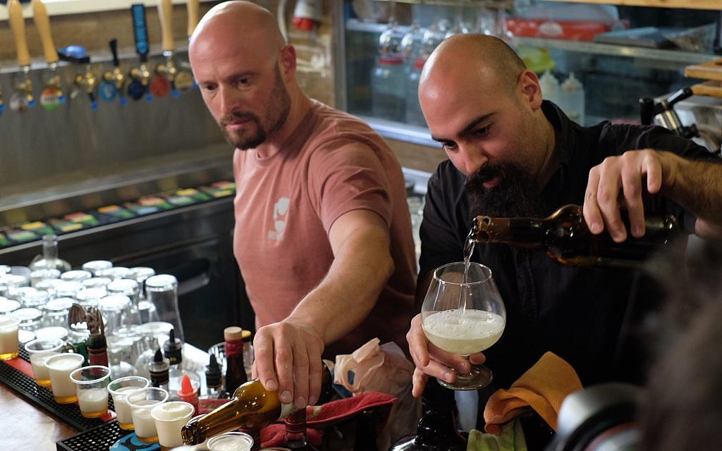 Lion Black, left, and Shmuel Naky, right, pour beer and mead made with 3,000-year-old yeast that were brewed as part of an archaeological-microbiological study, on May 22, 2019. (Judah Ari Gross/Times of Israel)