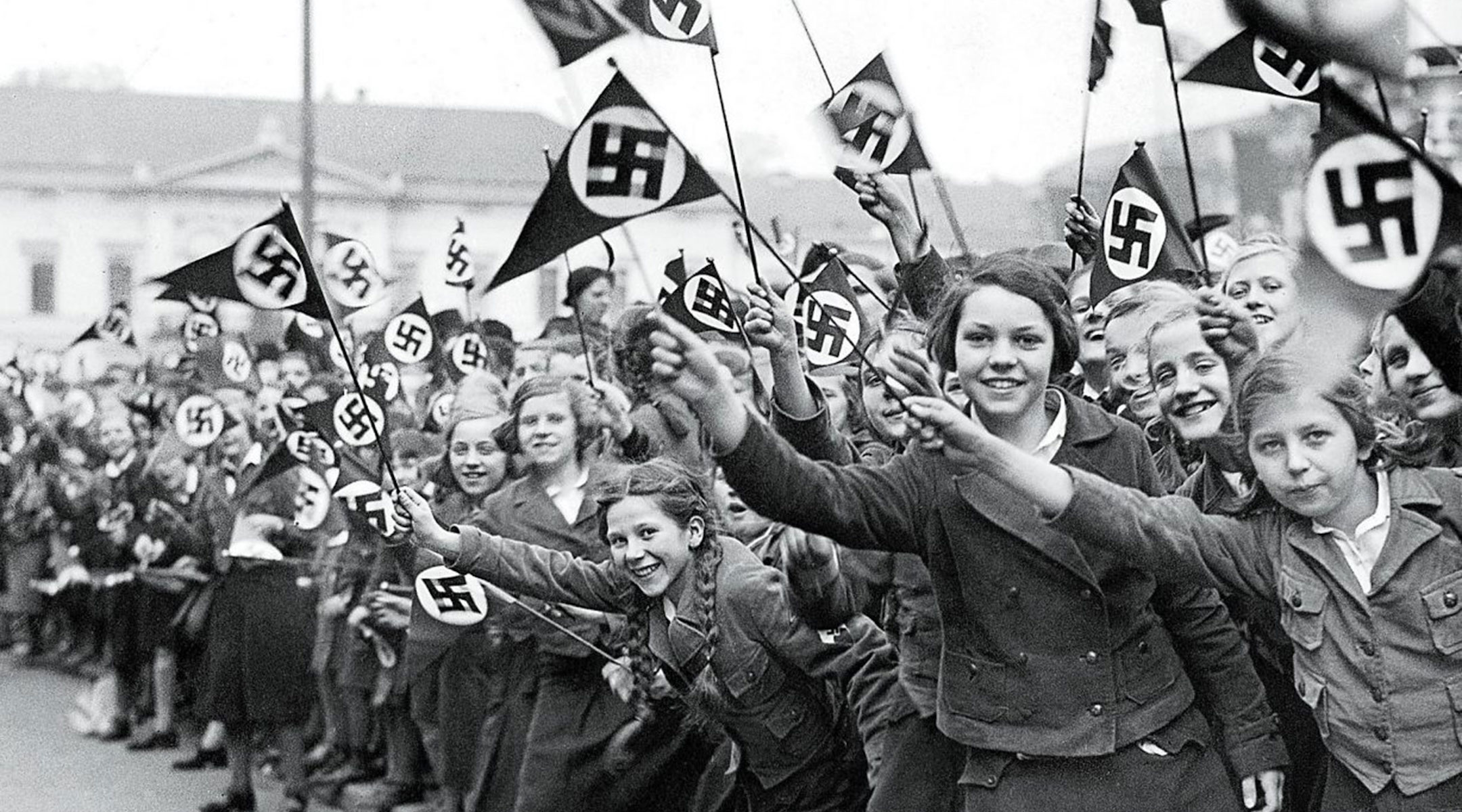 Austrian members of the League of German Girls wave Nazi flags in support of the German annexation of Austria, in Vienna, March 1938. (US Holocaust Memorial Museum)