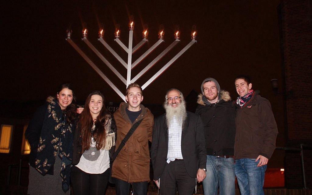 Rabbi Fishel Cohen with Jewish students at a candle lighting ceremony in Hanukka in Birmingham, the United Kingdom on December 24, 2014. (Courtesy of Rabbi Fighsel Cohen /The Birmingham Tab/via JTA)
