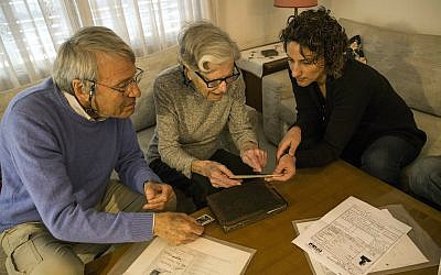 In this photo from April 23, 2019, Israeli Holocaust survivors Rachel Zeiger 91, center, and her brother Moshe Akerman 84, left, speak with Orit Noiman, head of Yad Vashem's collection and registration center, at their home in the Tel Aviv suburb of Ramat Gan. (AP Photo/Tsafrir Abayov)