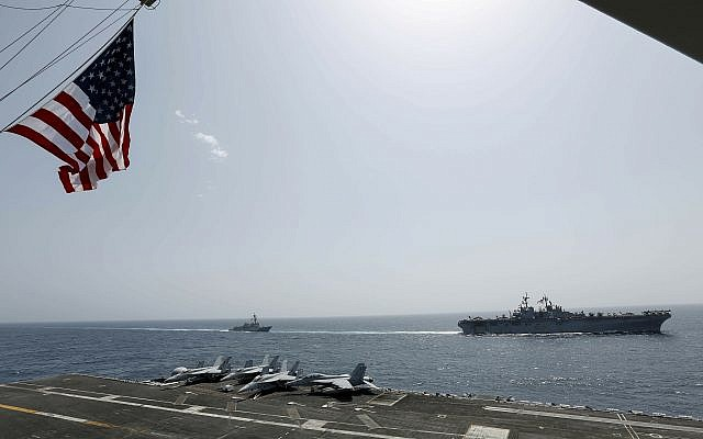 In this Friday, May 17, 2019, photo, released by the US Navy, the amphibious assault ship USS Kearsarge, right, and the Arleigh Burke-class guided-missile destroyer USS Bainbridge, left, are seen from the Nimitz-class aircraft carrier USS Abraham Lincoln as they sail in the Arabian Sea. (Mass Communication Specialist Seaman Michael Singley, US Navy via AP)