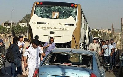 Police inspect a car and a bus that were damaged by a bomb, in Cairo, Egypt, March 19, 2019. (AP Photo/Mohammed Salah)