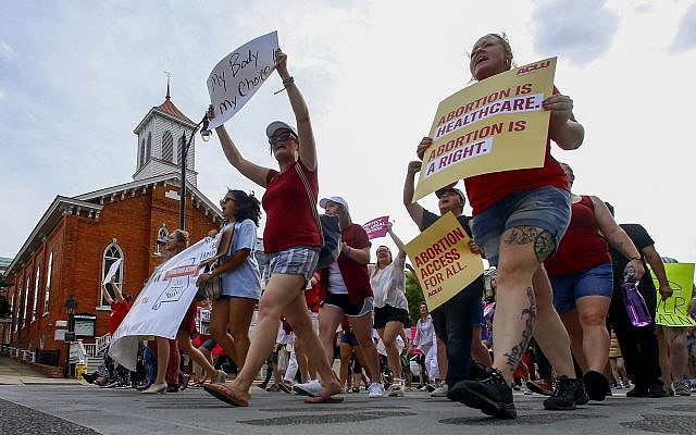Protesters for women's rights march past Dexter Avenue Baptist Church to the Alabama Capitol to protest a law passed last week making abortion a felony in nearly all cases with no exceptions for cases of rape or incest, Sunday, May 19, 2019, in Montgomery, Ala. (AP Photo/Butch Dill)