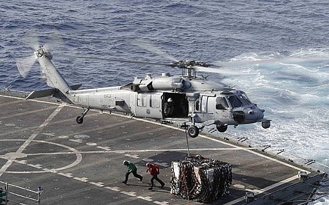 An MH-60S Sea Hawk helicopter transports cargo from the fast combat support ship USNS Arctic to the Nimitz-class aircraft carrier USS Abraham Lincoln during a replenishment-at-sea operation in the Arabian Sea, May 19, 2019. (Mass Communication Specialist 3rd Class Darion Chanelle Triplett/U.S. Navy via AP)