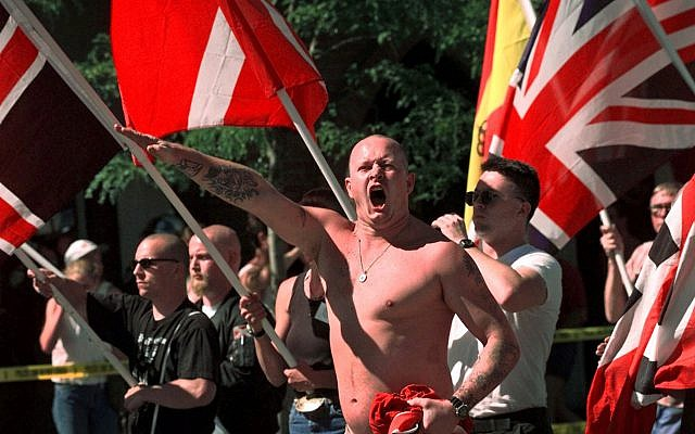 In this July 18, 1998, file photo, Karl Wolf raises his arm in a Nazi salute as he marches through the streets of Coeur d'Alene, Idaho, where scores of police in riot gear stood between parading white supremacists and protesters who jeered at the Aryan Nations marchers. (AP Photo/Elaine Thompson, File)