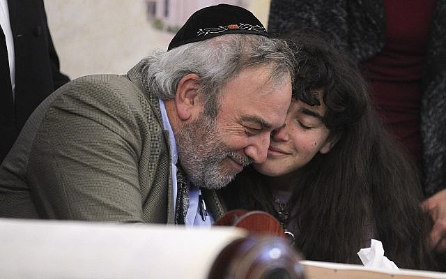 Howard Kaye, center, and his daughter Hannah Kaye, hug after the final letter is inked into the new Torah scroll dedicated to wife and mother Lori Kaye, who was killed when a gunman attacked the Chabad of Poway on April 27, 2019, during a celebration for the new scroll, foreground, at the synagogue on May 22, 2019, in Poway, California. (Hayne Palmour IV/The San Diego Union-Tribune via AP)