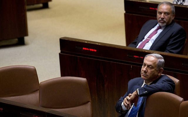 Prime Minister Benjamin Netanyahu (front) and former Defense Minister Avigdor Liberman sit in the Knesset, May 23, 2016. (AP Photo/Sebastian Scheiner, File)