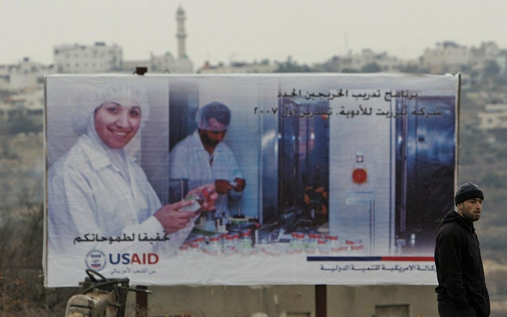 A Palestinian man stands next to an USAID billboard in the southern West Bank city of Halhoul, December 17, 2007. (AP Photos/Kevin Frayer)