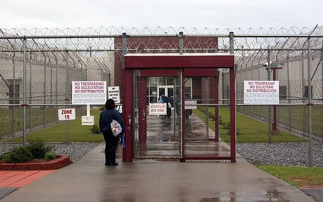 Illustrative: This April 13, 2009 photo shows an employee of Immigration and Customs Enforcement's Stewart Detention Center in Lumpkin, Georgia, waiting for the front gate to be opened so she can enter. (AP Photo/Kate Brumback)