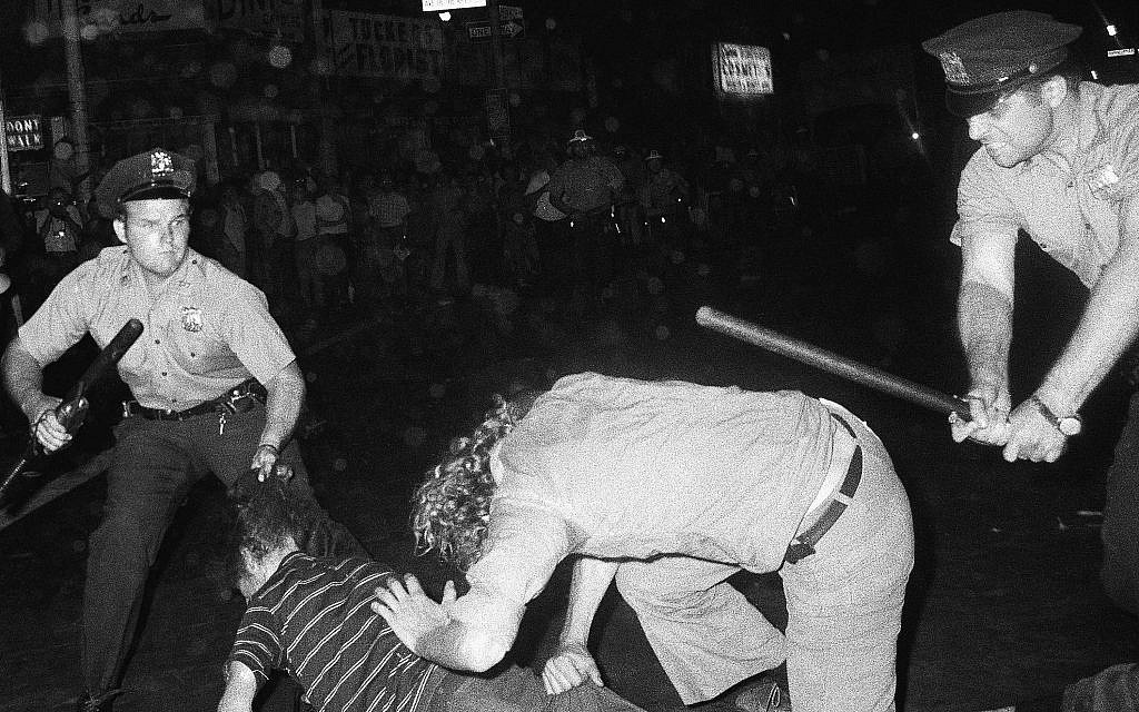 Illustrative: In this August 31, 1970 file photo, a NYPD officer grabs a youth by the hair as another officer clubs a young man during a confrontation in Greenwich Village after a Gay Power march in New York. (AP Photo/File)