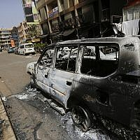 Illustrative: A soldier walks past a burnt car in front of Cappuccino cafe in Ouagadougou, Burkina Faso, after it was attacked by al-Qaeda-linked extremists, January 17, 2016. (Sunday Alamba/AP)