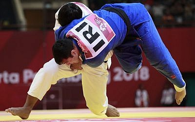 Uzbekistan's Bekmurod Oltiboev, in white, competes against Iran's Javad Mahjoub during their men's +100 kg judo bronze medal match at the 18th Asian Games in Jakarta, Indonesia, Friday, August 31, 2018. (AP/Dita Alangkara)