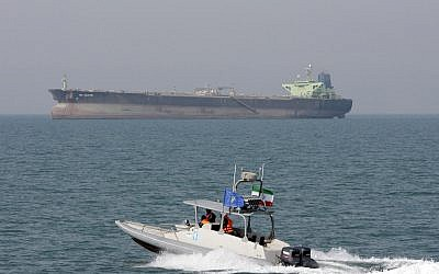 An Iranian Revolutionary Guard speedboat maneuvers in the Persian Gulf while an oil tanker is seen in background, July 2, 2012. (Vahid Salemi/AP)