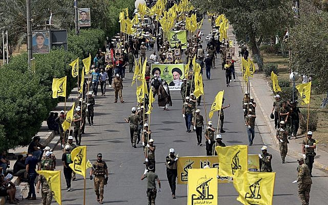 "In this June 8, 2018 file photo, Iraqi Popular Mobilization Forces march as they hold their flag and posters of Iraqi and Iranian Shiites spiritual leaders during ""al-Quds"" or Jerusalem Day, in Baghdad, Iraq. (AP Photo/Hadi Mizban)"