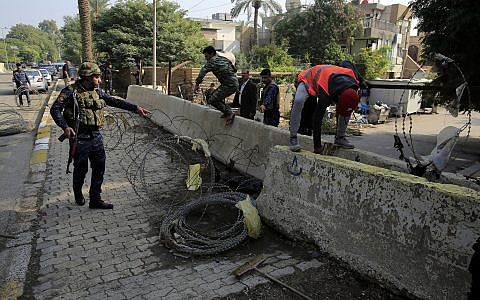 Iraqi security forces remove concrete blast walls leading to the heavily guarded Green Zone in Baghdad, Iraq, Nov. 27, 2018. (AP/Karim Kadim)