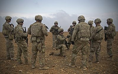 In this Nov. 7, 2018, photo released by the US Army, US soldiers gather for a brief during a combined joint patrol rehearsal in Manbij, Syria (US Army photo by Spc. Zoe Garbarino via AP)