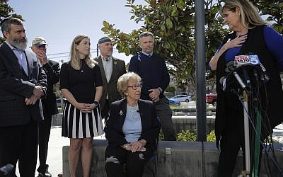 Eva Schloss, center, listens to Charlene Metoyer, a board member of the Newport-Mesa Unified School District during a news conference Thursday, March 7, 2019, in Newport Beach, California. Schloss has met with Southern California high school students who were photographed giving Nazi salutes around a swastika formed by drinking cups at a party. Schloss says the students apologized for their behavior and indicated they didn't realize what it really meant. (AP Photo/Jae C. Hong)