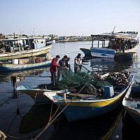Palestinian fishermen clean a net after a night fishing trip, in the Gaza Seaport on April 3, 2019. (AP Photo/Khalil Hamra)