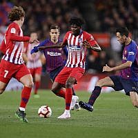 Atletico forward Antoine Griezmann, left, Atletico midfielder Thomas Partey, and Barcelona's Sergio Busquets, right, vie for the ball during a Spanish La Liga soccer match between FC Barcelona and Atletico Madrid at the Camp Nou stadium in Barcelona, Spain, Saturday April 6, 2019. (AP Photo/Manu Fernandez)