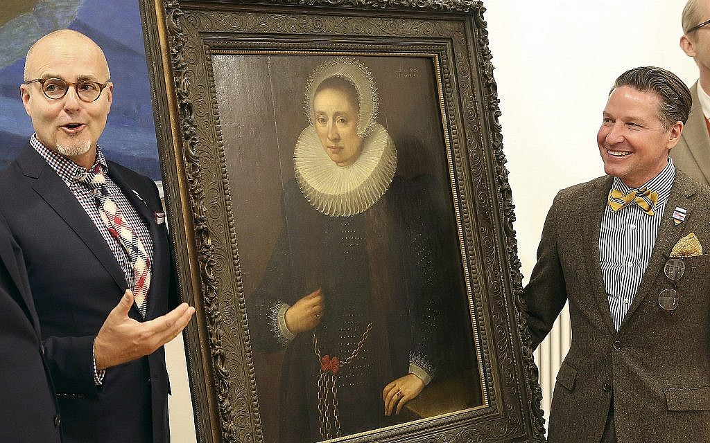 "A Los Angeles couple, Craig Gilmore, left, and David Crocker, pose in front of a 17th painting, ""Portrait of a Lady"" by the Flemish artist Melchior Geldorp at the National Museum in Warsaw, Poland, April 5, 2019. (Czarek Sokolowski/AP)"