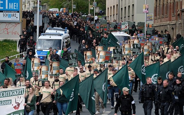 Protesters march with flags during a demonstration of the far-right party 'The third way' in Plauen, Germany, Wednesday, May 1, 2019. (Sebastian Willnow/dpa via AP)