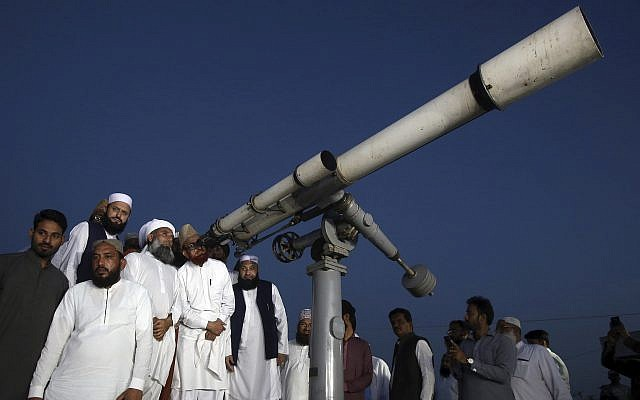 Clerics of Pakistan's Moon Sighting Committee search the sky with a telescope for the new moon that signals the start of the Muslim fasting month of Ramadan, in Karachi, May 5, 2019. (AP/Fareed Khan)