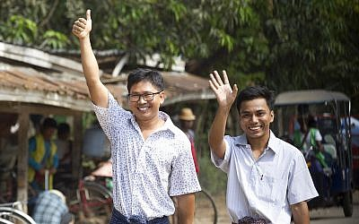 Reuters journalists Wa Lone, left, and Kyaw She Oo wave as they walk out from Insein Prison after being released in Yangon, Myanmar, May 7, 2019 (AP Photo/Thein Zaw)