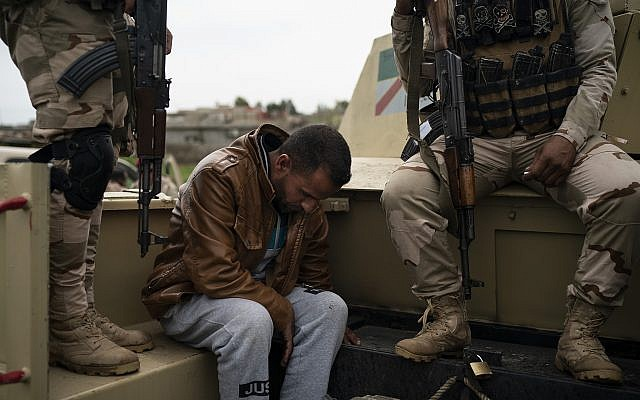 In this April 5, 2019 photo, a man is taken for questioning by Iraqi army 20th division soldiers during a raid in Badoush, Iraq. (AP Photo/Felipe Dana)