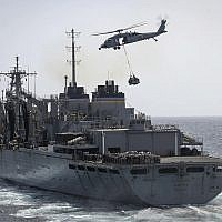 In this Sunday, May 19, 2019, photo released by the US Navy, an MH-60S Sea Hawk helicopter transports cargo from the fast combat support ship USNS Arctic to the Nimitz-class aircraft carrier USS Abraham Lincoln during a replenishment-at-sea in the Arabian Sea.(Mass Communication Specialist 3rd Class Jeff Sherman/US Navy via AP)