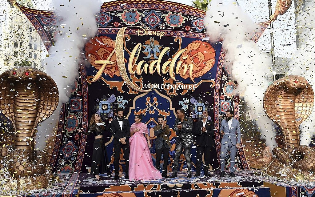 """Nasim Pedrad, from left, Marwan Kenzari, Naomi Scott, Mena Massoud, Will Smith, Navid Negahban and Numan Acar react as confetti falls at the premiere of """"Aladdin"""" on May 21, 2019, at the El Capitan Theatre in Los Angeles. (Photo by Chris Pizzello/Invision/AP)"""