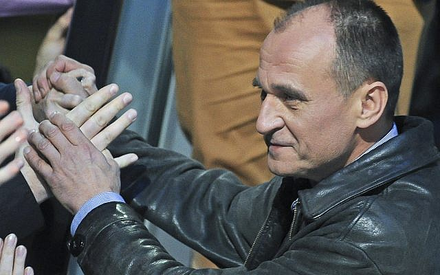 Pawel Kukiz, the leader of Kukiz'15, shakes hands with supporters after a televised parliamentary elections debate in Warsaw, Poland, October 20, 2015. (AP Photo/Alik Keplicz)