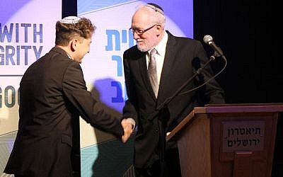 Newly ordained Rabbi Daniel Atwood is congratulated by Rabbi Daniel Landes at the Jerusalem Theater, on May 26, 2019. (Sam Sokol/JTA)