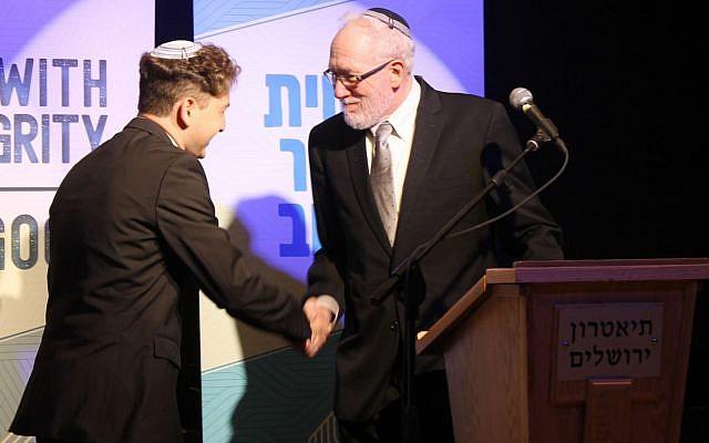 Newly ordained Rabbi Daniel Atwood is congratulated by Rabbi Daniel Landes at the Jerusalem Theater, on May 26, 2019. (Sam Sokol/JTA)