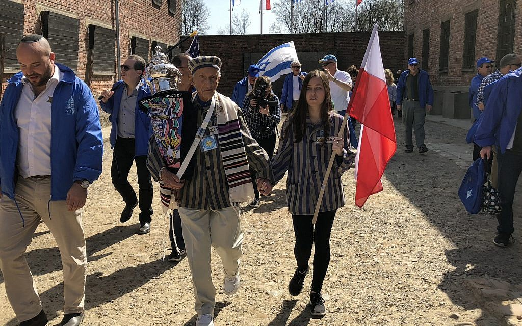 Edward Mosberg, holding a Torah scroll, takes part in the March of the Living in 2017 at the former Nazi death camp Auschwitz in Poland. (Courtesy of From the Depths via JTA)