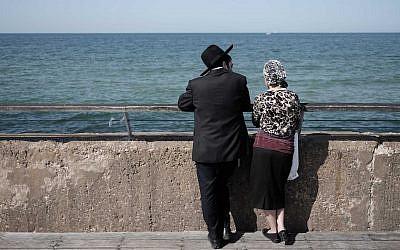 Illustrative: an ultra-Orthodox Jewish couple enjoys a sunny afternoon at the Tel Aviv port, February 5, 2016. (Tomer Neuberg/Flash90)