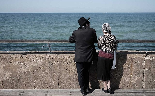 Illustrative: an ultra-Orthodox Jewish couple enjoys a sunny afternoon at the Tel Aviv port, February 5, 2016. (Tomer Neuberg/Flash90)