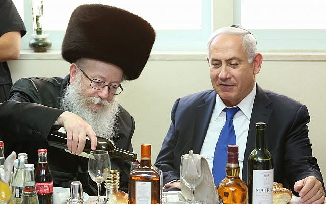 Prime Minister Benjamin Netanyahu is hosted by Minister of Health Yaakov Litzman of the United Torah Judaism party (left), at a meal to celebrate the birth of Litzman's grandson, June 18, 2017. (Shlomi Cohen/FLASH90)