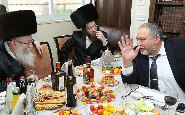Then-Defense Minister Avigdor Liberman is hosted by then-Minister of Health Yaakov Litzman (left), at a meal to celebrate the birth of Litzman's grandson, June 18, 2017. (Shlomi Cohen/FLASH90)