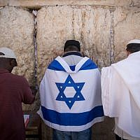 A man wearing an Israeli flag prays at the Western Wall in the Old City of Jerusalem, September 17, 2017.(Yonatan Sindel/Flash90)