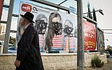 An ultra-Orthodox Jewish man walks past a vandalized billboard in Jerusalem where women's faces have been blotted out, November 2, 2017. (Noam Revkin Fenton/Flash90)