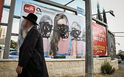 An ultra-Orthodox Jewish man walks past a vandalized billboard in Jerusalem where women's faces have been blotted out, November 2, 2017. (Noam Revkin Fenton/Flash90)