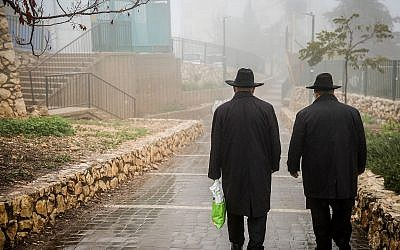 Illustrative: Ultra-Orthodox men walking in the rain and fog in Safed, December 18, 2018. (David Cohen/Flash90)