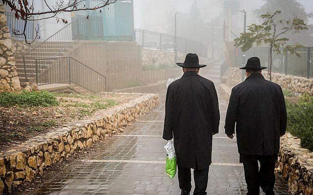 Illustrative: Ultra-Orthodox men walking in the rain and fog in Safed, December 18, 2018. (David Cohen/Flash90)
