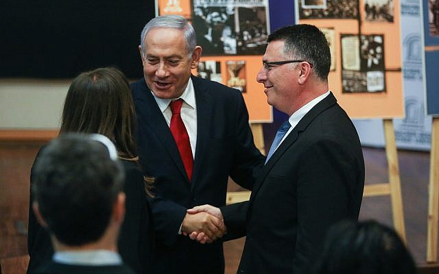 Prime Minister Benjamin Netanyahu shakes hands with Gideon Sa'ar during a Likud party meeting at the Menachem Begin Heritage Center in Jerusalem on March 11, 2019. (Yonatan Sindel/Flash90)