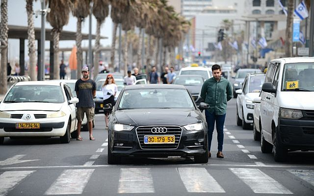 People stand still in Tel Aviv, as a two-minute siren is sounded across Israel to mark Holocaust Remembrance Day on May 2, 2019. (Tomer Neuberg/Flash90)