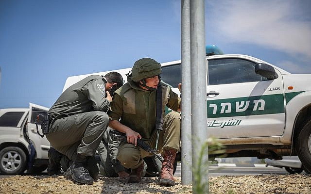 Illustrative: Israeli security forces take cover on the side of a highway near the Gaza border as the incoming rocket siren is heard on May 5, 2019. (Noam Rivkin Fenton/Flash90)