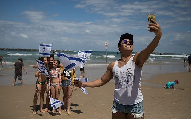 People at Bugrashov Beach in Tel Aviv watch the military airshow on Israel's 71st Independence Day, May 9, 2019. (Hadas Parush/Flash 900