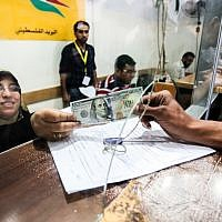 Palestinians receive their financial aid as part of $480 million in aid allocated by Qatar, at a post office in Gaza City on May 19, 2019. (Abed Rahim Khatib/Flash90)